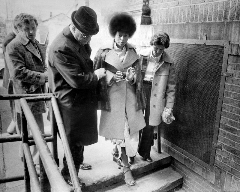 """UNITED STATES - JANUARY 29: In a caravan of eight cars bearing heavily armed state police and county officers, JoAnne Chesimard, the reputed """"soul"""" of the Black Liberation Army, was taken chained handcuffs and leg irons from Riker's Island prison in New York City ot the Middlesex County jail to await trail in the murder of state trooper Werner Foerster. (Photo by Frank Hurley/NY Daily News Archive via Getty Images)"""
