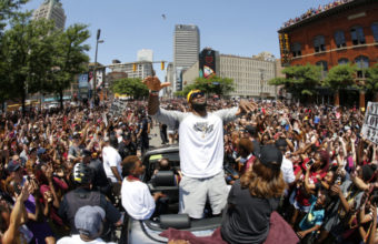 Cleveland Cavaliers' LeBron James, center, stands in the back of a Rolls Royce as it makes it way through the crowd lining the parade route in downtown Cleveland, Wedensday, June 22, 2016, celebrating the Cleveland Cavaliers' NBA Championship. (AP Photo/Gene J. Puskar) ORG XMIT: OHGP108